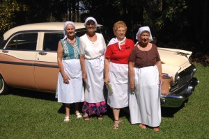 """Ladies dressed for the World day of Prayer in their """"Cuban"""" themed costumes in front of a 60 year old car."""